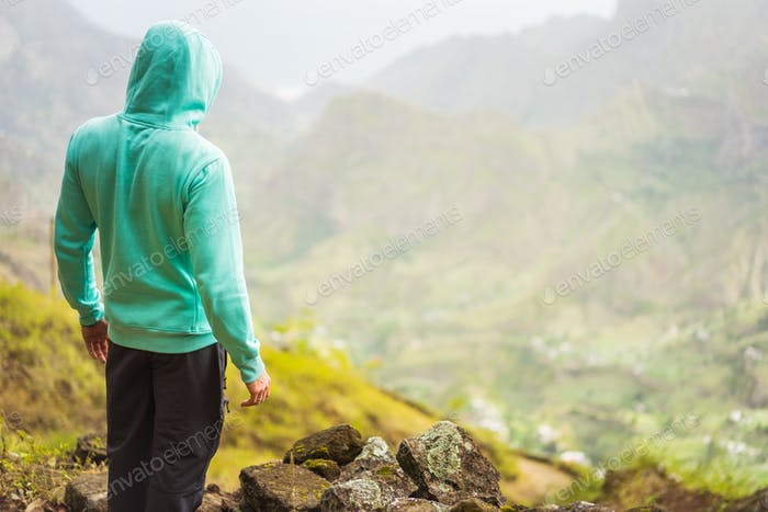 Tourist in hoodie in front of rural landscape with mountains, on the way of the Paul Valley. Santo