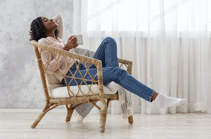 Home Harmony. Young African Lady Relaxing With Cup Of Coffee In Chair