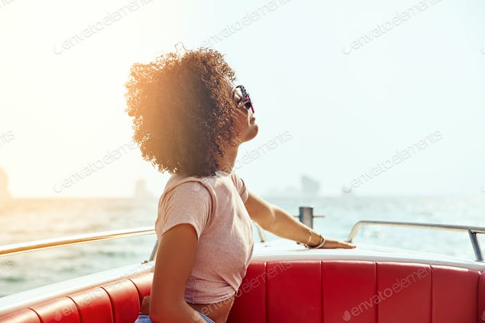 Smiling young woman sitting on a boat during summer vacation