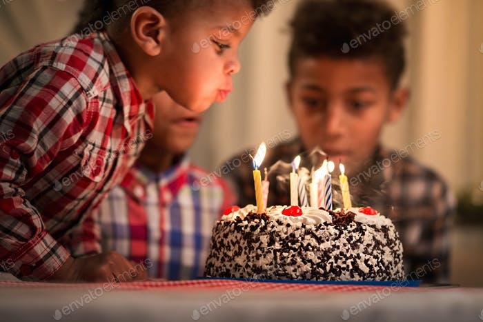Black toddler blowing candles out.
