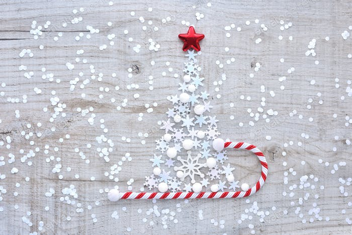 Christmas tree made of snowflakes on a light wooden background.