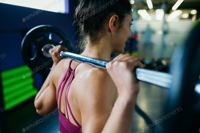 Athletic woman in gym lifting weights at the gym