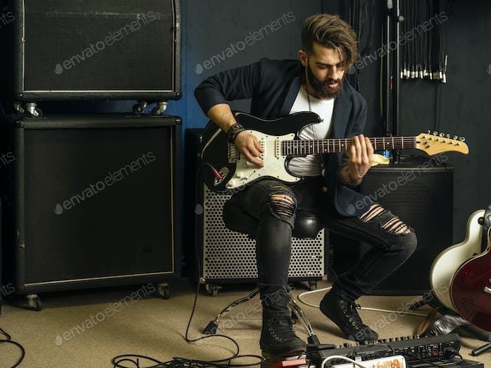 Handsome man playing an electric guitar in a studio