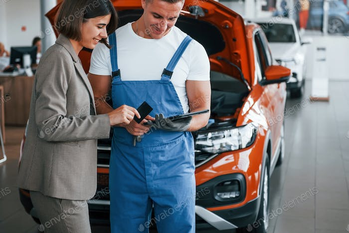 Two people. Man repairing woman's automobile indoors. Professional service