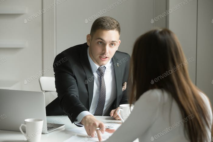 Young businessman is pointing to a mistake in a paper