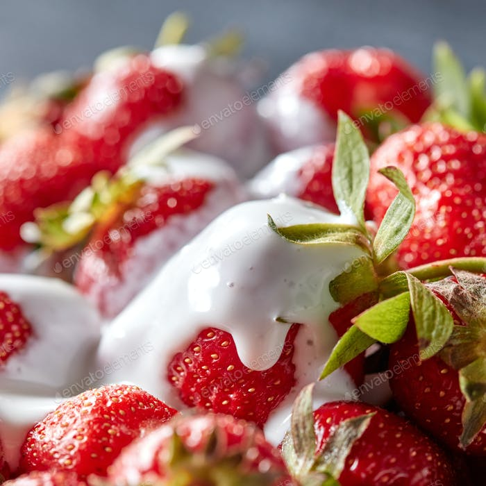 Closeup of juicy organic strawberries with green leaves and fresh cream. Healthy dessert