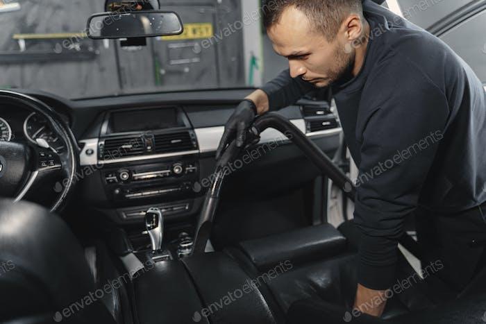 Mann, der eine Autokabine in einer Garage abhaugt