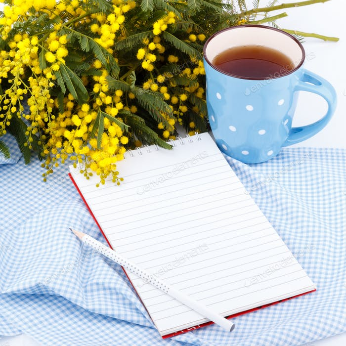 Mimosa flowers, notepad and cup of tea