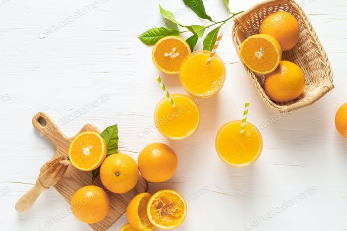 Orange juice. Freshly squeezed juice in glasses and fresh fruits with leaves, view from above