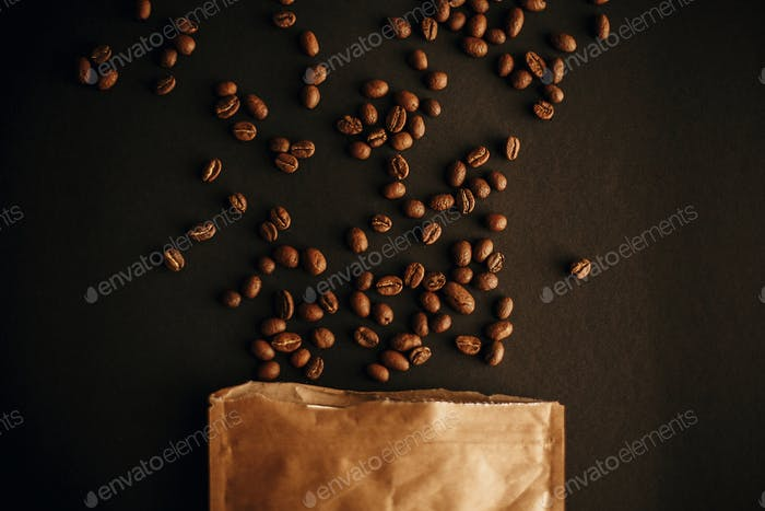 Coffee beans scattered from paper pack on black background Flat lay