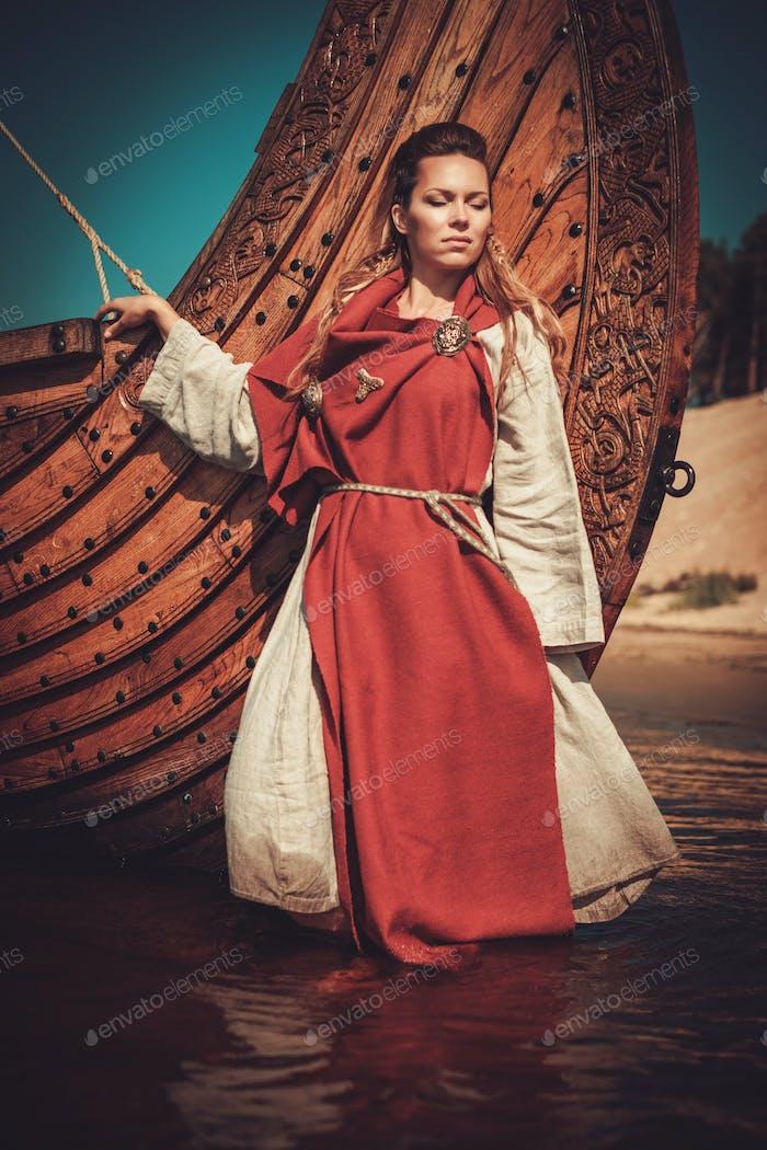 Mujer vikinga en ropa tradicional cerca de drakkar