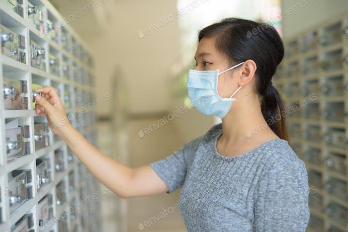 jóvenes asiático mujer con máscara comprobando buzón
