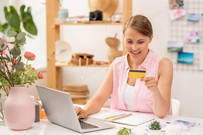 Happy young female online shopper with plastic card entering its number