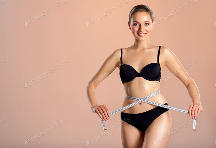 Young smiling woman with tape and a beautiful, healthy body. Sexy woman measuring her perfect body.