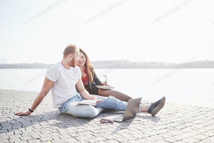 Два студента парень и девушка сидят на открытом воздухе и наслаждаются ноутбуком, учатся на открытом воздухе