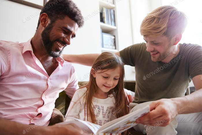 Same Sex Male Couple Reading Book With Daughter At Home Together Whilst Tickling Her