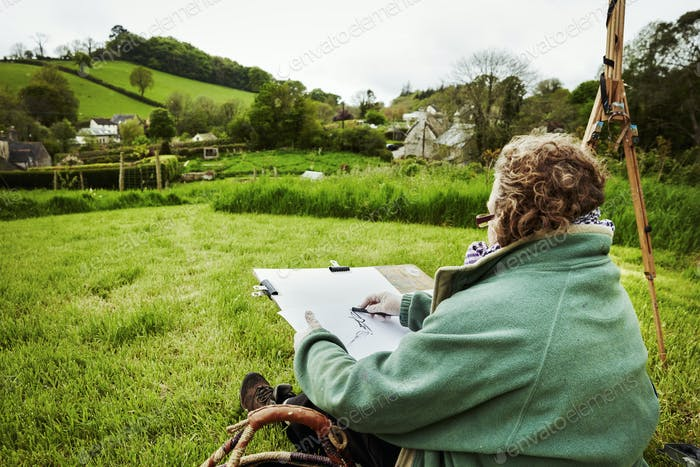 A woman artist sketching with charcoal on paper, sitting on the ground outdoors.