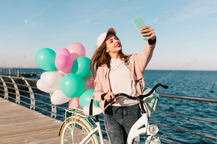 Charming female cyclist in a pink cap and windbreaker smiling and taking selfie on the sea backgroun