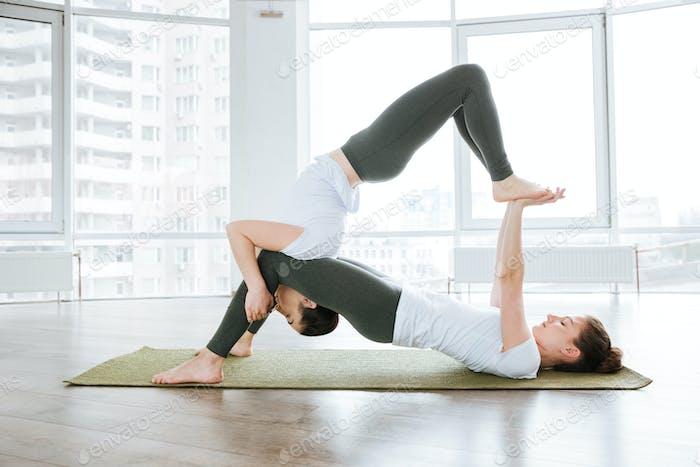 Two pretty young women doing acro yoga