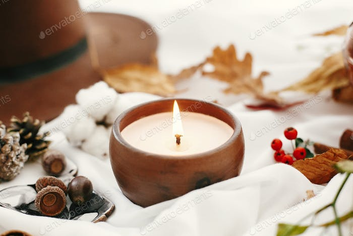 Hygge lifestyle. Candle, berries, fall leaves, herbs, acorns, nuts and brown hat on white fabric