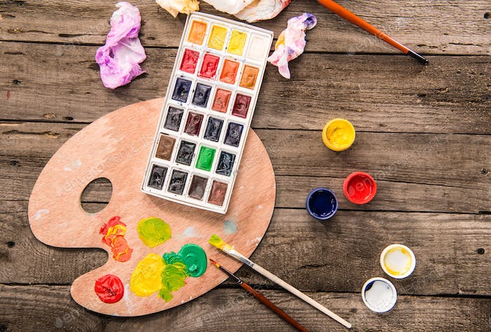 top view of paints, paintbrushes and palette on table