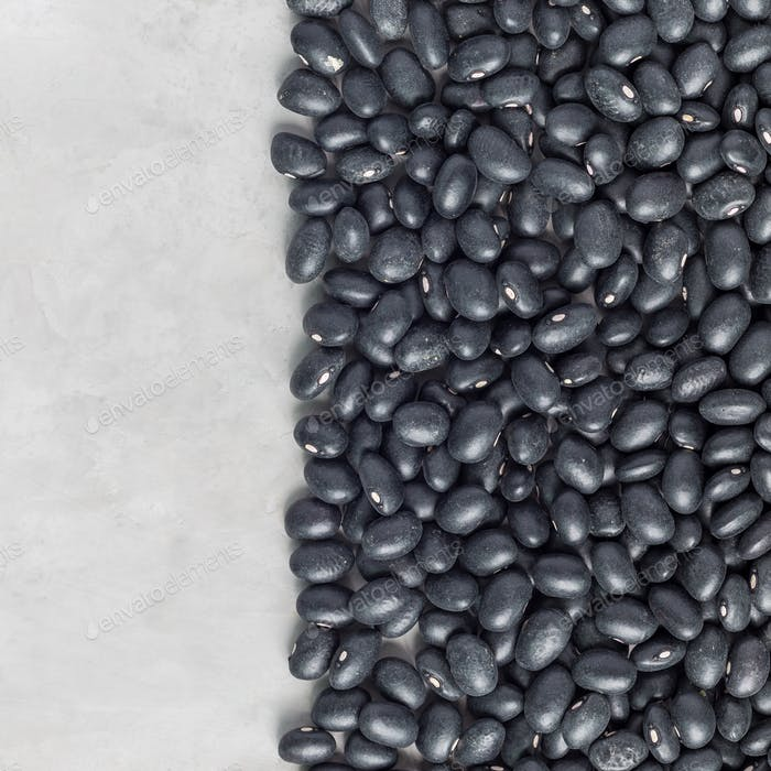 Uncooked dry black beans on a gray concrete background, top view, square format