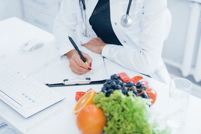 Female nutritionist in white coat sitting indoors in the office at workplace