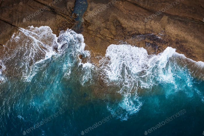 Rocky shore of the island of Tenerife. Aerial drone photo of ocean waves reaching shore