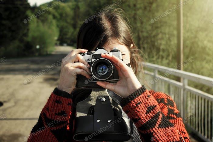 woman hipster traveler holding analog photo camera in mountains