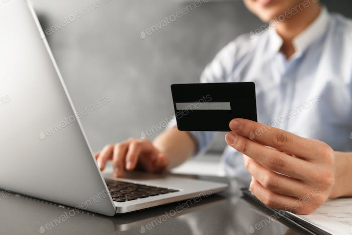 Close up of a man holding plastic credit card