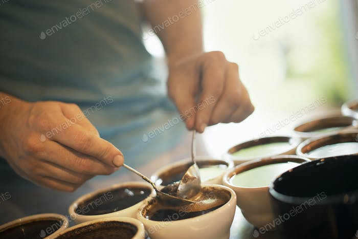 Person sampling coffee in a coffee processing shed, coffee in small pots to test the blend.