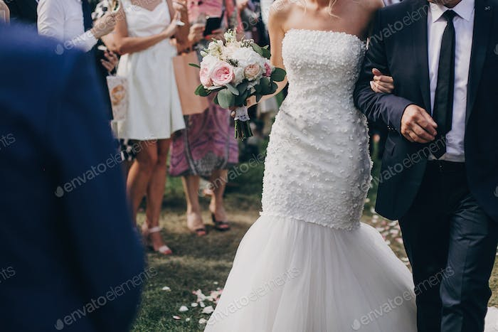 Father walking with daughter, beautiful stylish bride