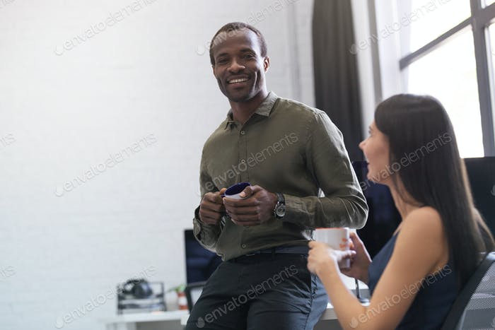 Happy afro american guy chatting with a female colleague