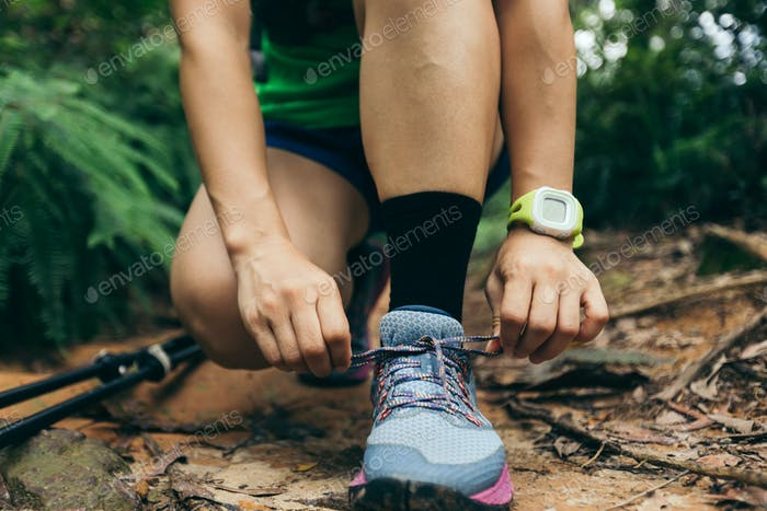Ultra marathon runner tying shoelace in rainforest