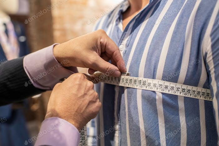 tailor making the measurement of his client for making a suit