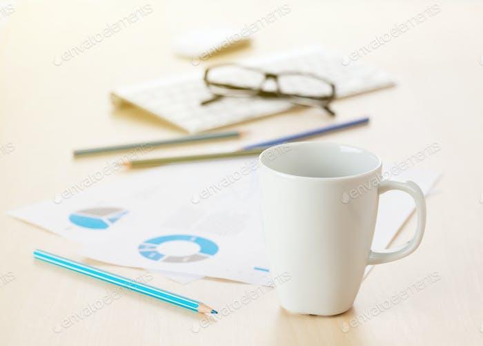 Büroarbeitsplatz mit Kaffee, Zubehör und Berichte