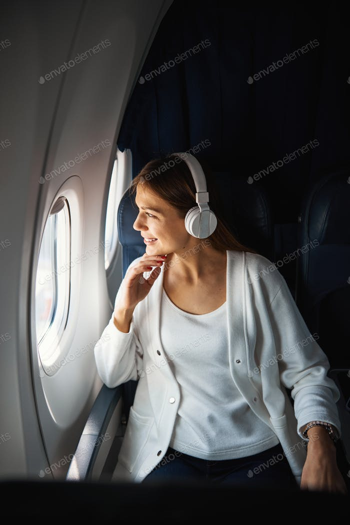 Contented lady looking at the clouds during the flight