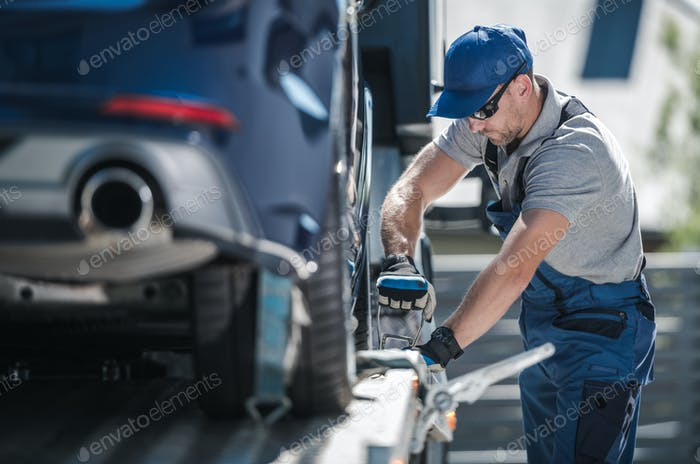 Towing Company Worker Securing Vehicle on the Truck Platform