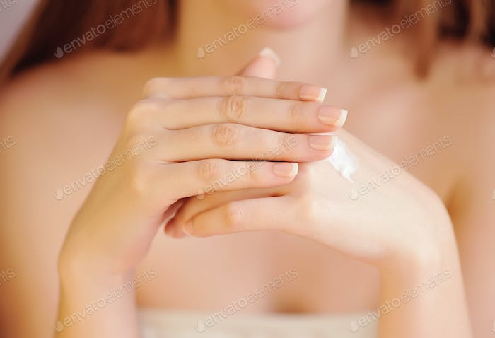 Young woman applies cream on her hands after bath. Focus on hand