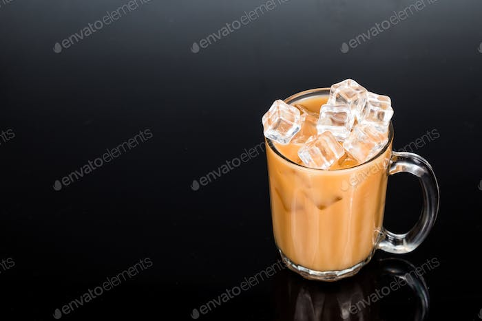 Refreshing ice cold tea with milk in transparent glass in black background