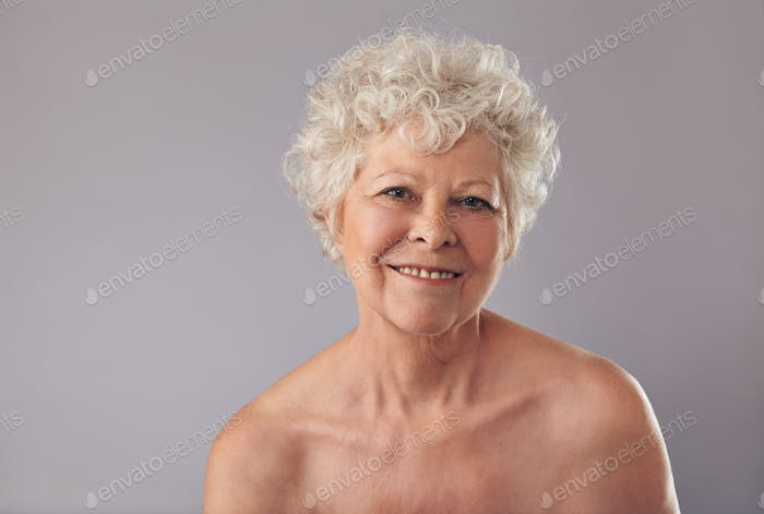 Senior woman smiling on grey background