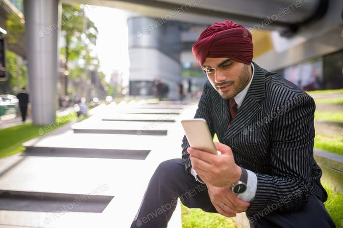 Indian businessman sitting outdoors in city while using mobile phone