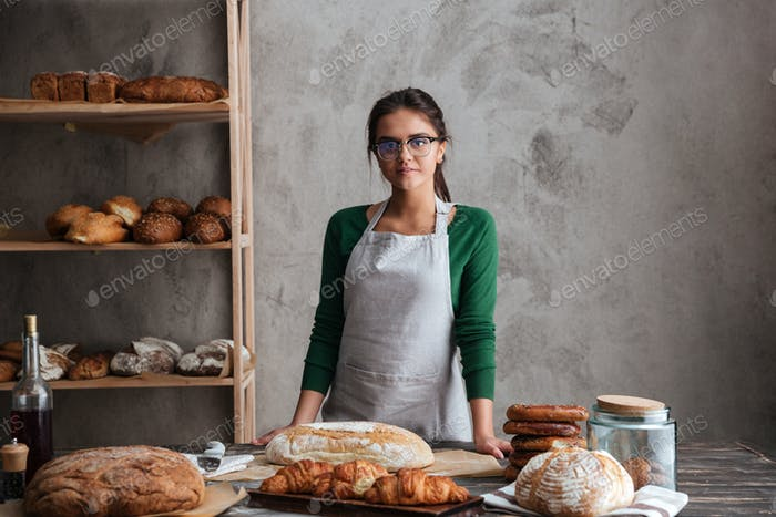 Happy young lady baker standing at bakery near bread