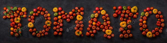 Tomato word made with ripe tomatoes on a black background, creative flat lay healthy food concept