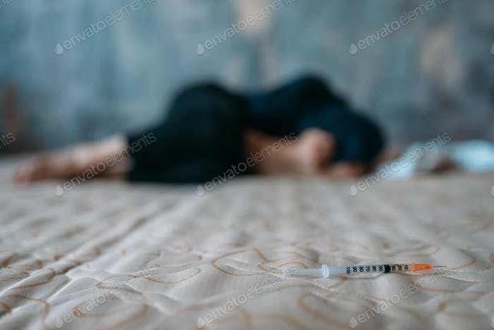 Female junkie sleeping in bed after dose