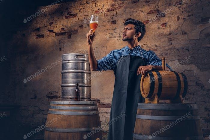 Experte Brauer in der Schürze, die in der Nähe von Fässern steht, überprüft die Qualität des gebrauten Getränks in der Brauerei.