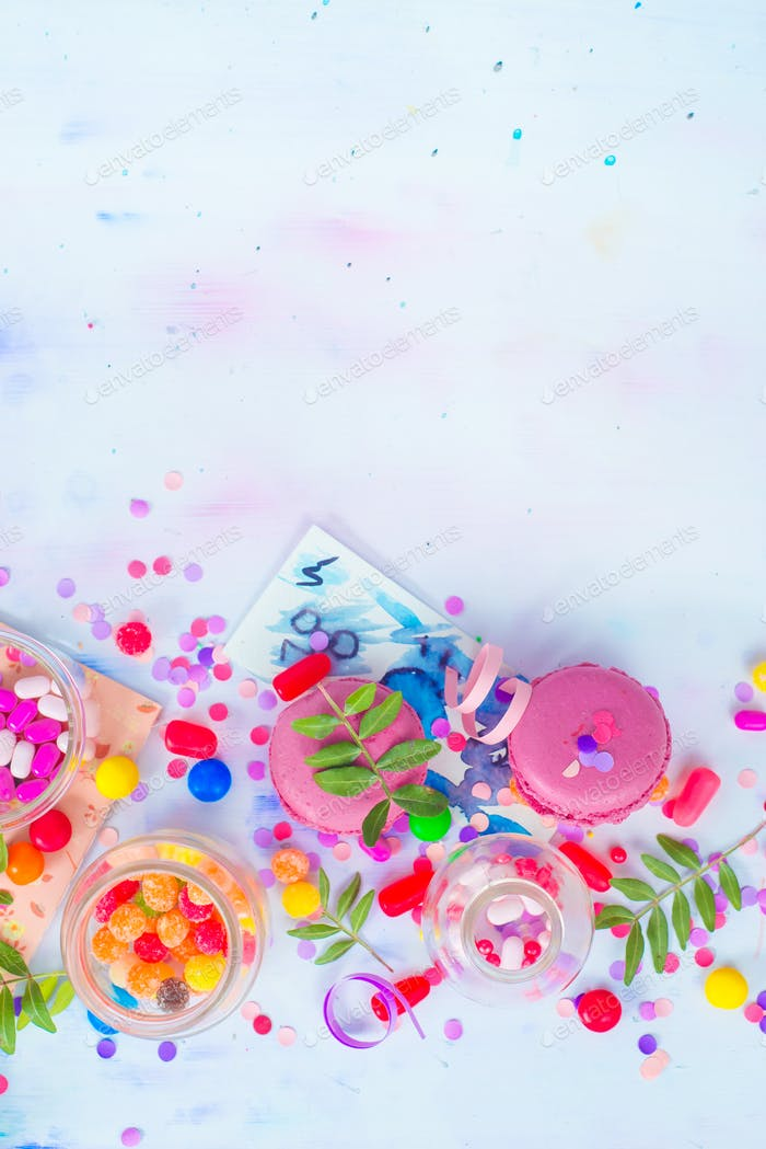 Colorful celebration flat lay with party supplies, confetti and sweets. Pink macarons overhead scene