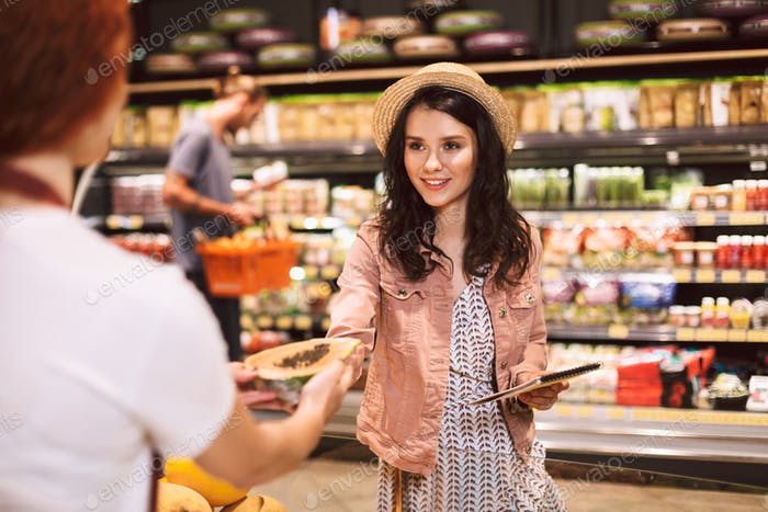 Beautiful smiling girl in hat with shopping list in hand happily