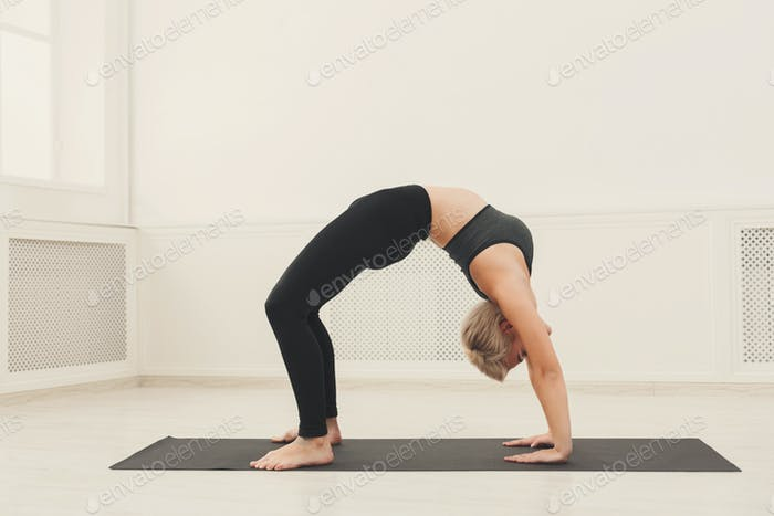 Woman training yoga in table top pose.