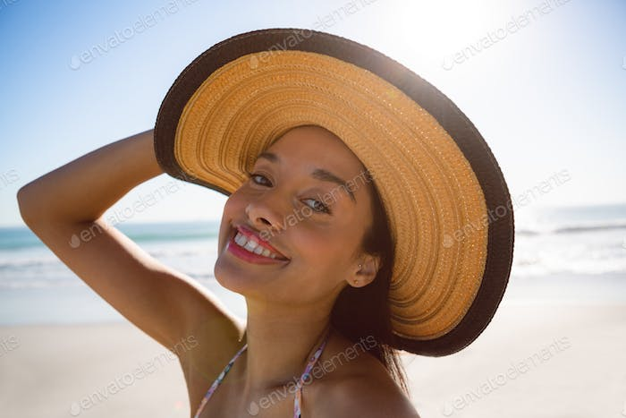 Portrait of beautiful mixed race woman in hat standing on the beach